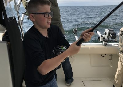 Boy catching fish on Xstream Charter Trip