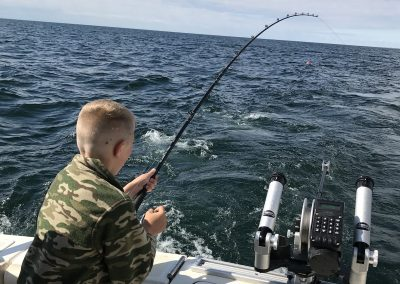 Boy catching fish on Charter Fishing with Xstream Charters on Lake Michigan